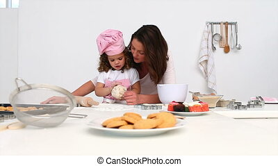 Mother baking cookies with her daughter in the kitchen