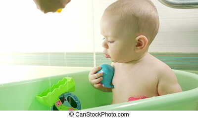 Mother bathing attractive baby. The boy is smiling and playing with colorful toys and water. Kid for about a year