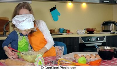 happy nice mother bind her little helper cute curly daughter green apron. Preparation to bake in kitchen. 4K