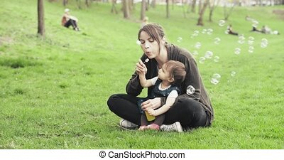 Mother blowing bubbles with baby girl.
