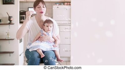 Mother blowing bubbles with her baby girl.