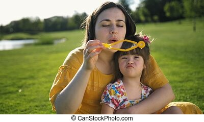 Mother blowing soap bubbles with special daughter