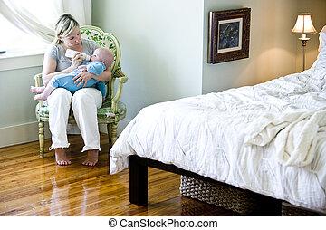 Mother bottle-feeding baby in bedroom