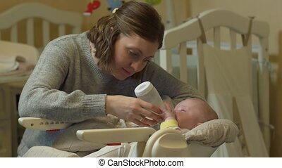 Mother Bottle Feeds Baby - Mother feeds bottle baby sitting...