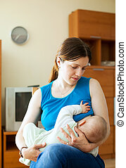 Mother breast feeding baby at home