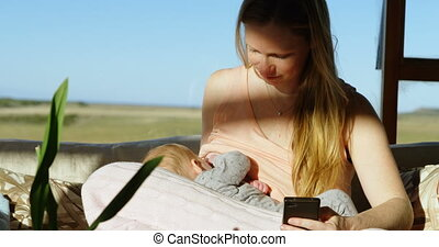 Mother breast feeding her baby while using mobile phone 4k -...