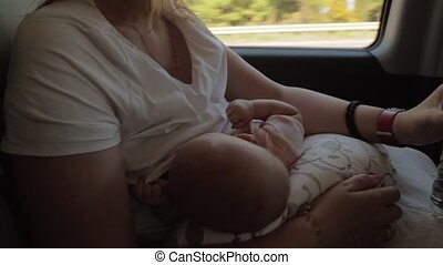 Mother breastfeeding baby and drinking water in the car