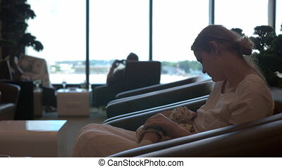 Mother breastfeeding baby daughter in airport lounge
