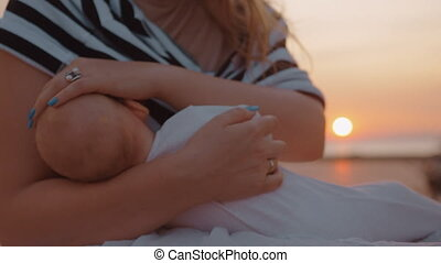 Mother breastfeeding baby outdoor at sunset