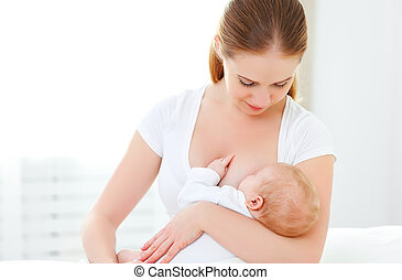 mother breastfeeding newborn baby in white bed