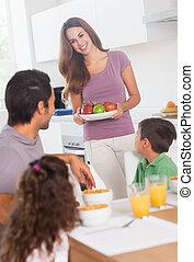 Mother bringing apples for breakfast