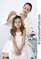 Mother brushing her daughter\'s hair