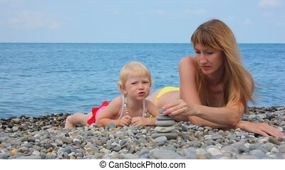 mother building stone stacks with little daughter in beach