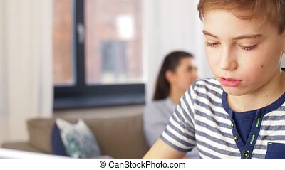 mother calling on phone and son learning at home - family, ...