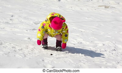 Small girl falls down on snow and mother cares of her