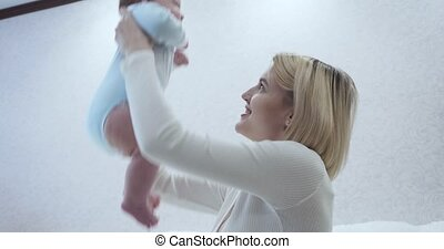 Mother carefully caresses her baby in her arms in the room...