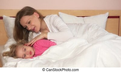 Mother caress her child girl lying in bed to make fall asleep.