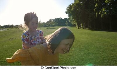 Mother carrying adorable happy daughter on back