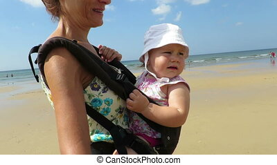 mother carrying baby in rucksack - mother carrying her one...