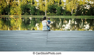 Mother carrying her child and looking at the lake