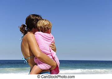 mother carrying her daughter on the beach