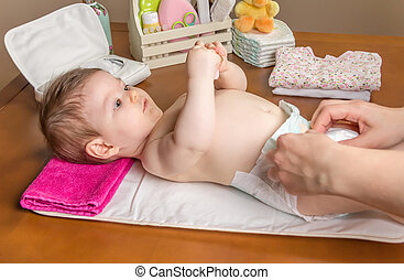 Mother changing diaper of adorable baby