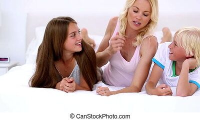 Mother chatting with her children at home in bedroom