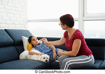 Mother Checking Temperature To Ill Daughter With Thermometer