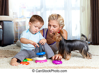 mother, child boy and pet dog playing together indoor -...
