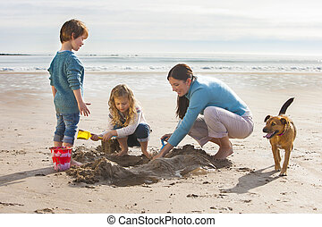 Mother Children and Pet Dog on the Beach - Mother playing on...