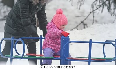 Mother circling her little daughter on the carousel in winter