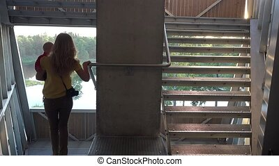 mother climb down stair in observation deck with baby on arm. 4K