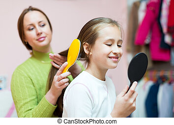 mother combing her daughter's hair - Young mother brushing ...