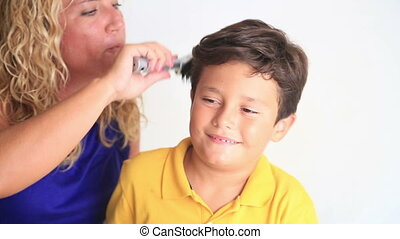 Mother combing son's hair