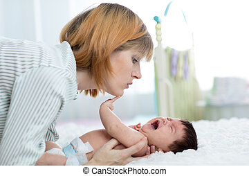 Mother comforts her crying newborn baby