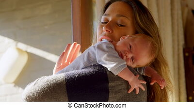 Mother consoling her baby boy in living room 4k - Mother ...