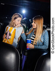 Mother Consoling Scared Daughter In Cinema Theater