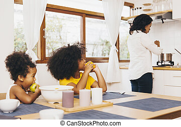 Mother cooking for her two children waiting for lunch. Single mom concept.