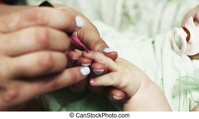 Mother cover nails of baby by bright pink lacquer. Manicure. Motherhood. Beauty