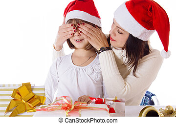 Mother covering daughter eyes with hands hiding Christmas gifts