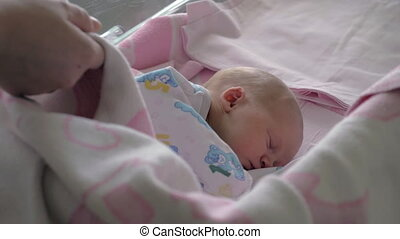 Mother covering sleeping baby with blanket