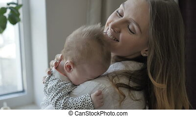 Mother cuddling her baby - Smiling woman cuddling her baby...