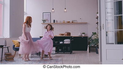 Mother dancing with daughter in the room