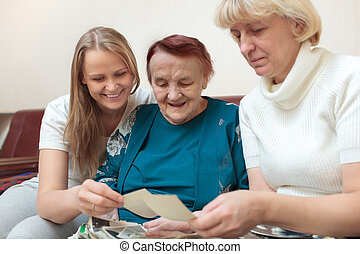 Mother, daughter and grandma looking at photos and...