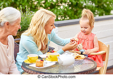 mother, daughter and grandmother eating at cafe