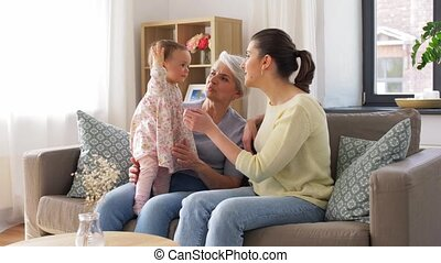 mother, daughter and grandmother on sofa at home - family, ...