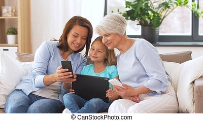 mother, daughter and grandmother with gadgets - family,...