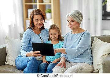 mother, daughter and grandmother with tablet pc