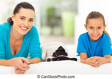 mother daughter and pet dog lying on bed