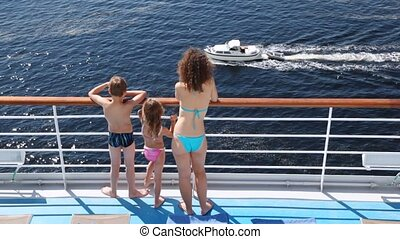 Mother, daughter and son look at powerboat floating nearby